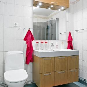 Przestrzeń łazienki wizualnie ociepla podumywalkowa szafka z drewnianym dekorem oraz korespondujący z nią pawlacz nad lustrem. Zdjęcia: Svenksfast.se