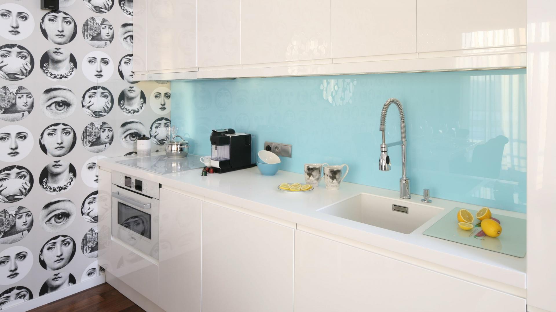 Ścianę nad blatem zdobi szkło w jasnoniebieskim kolorze. Projekt Anna Maria Sokołowska. Fot. Bartosz Jarosz.