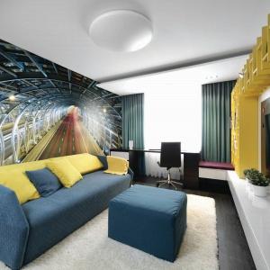 Wąskiemu salonowi z gabinetem dodano głębi za sprawą fototapety przedstawiającej zdjęcie długiego tunelu. Ściana harmonizuje kolorystycznie z meblami. Fot. Dekornik.