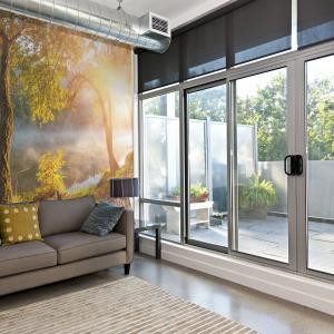 Na ścianie z fototapetą przedstawiającą piękny widok osnutego mgłą lasu o poranku stanęła sofa w kolorze ziemi z poduszkami korespondującymi barwą do kolorystyki ze zdjęcia. Fot. Dekornik.