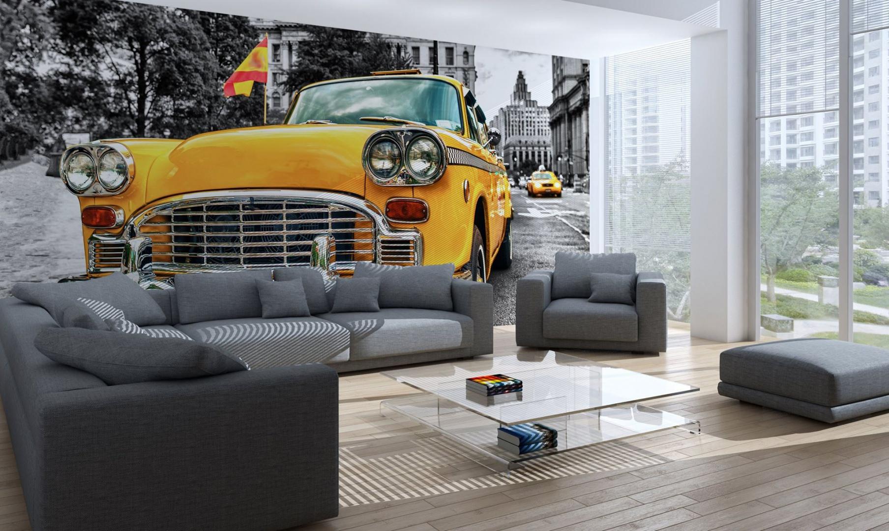 Salon zdominowany przez szarości ożywia mocno zółty element w postaci kolorowej taksówki na czarno-białym tle fotografii. Fot. Minka