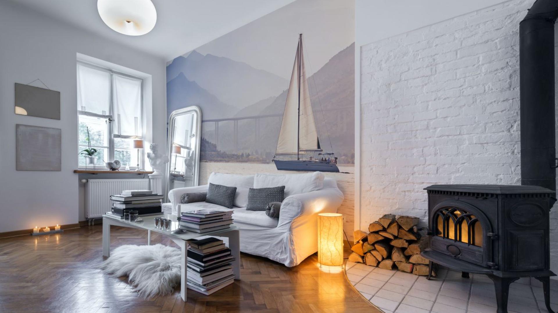 Na ścianie za kanapą widoczna jest panorama jeziora z płynącą po nim żaglówką. Kolorystyka fototapeta idealnie współgra ze skandynawską aranżacją wnętrza. Fot. Big-trix.