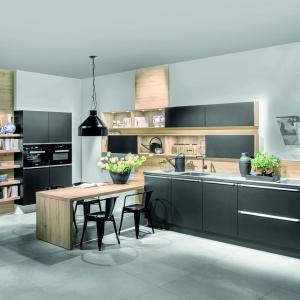 Nowoczesne kuchnia w familiarnym klimacie: model AV 6000 Schwarz. Czarne fronty ociepla dodatek drewna. Fot. Häcker