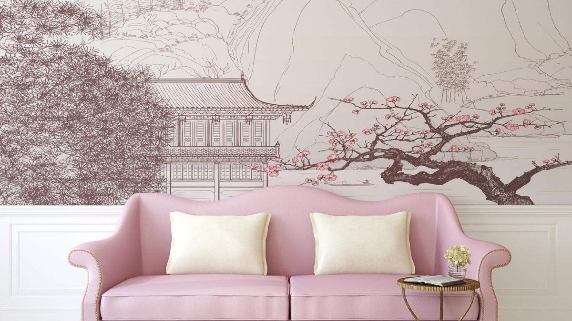 Stylizowana kanapa w pastelowym odcieniu różu pięknie harmonizuje z fototapetą przedstawiającą japońską grafikę z podkolorowanymi na różowo kwiatami sakury. Fot. Dekowizja.pl