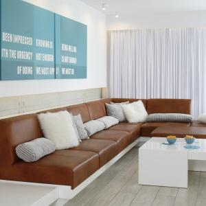 Minimalistyczna, bardzo czysta aranżacja salonu, w której rolę elementu dekoracyjnego pełni inspirująca grafika na ścianie. Chłodny wystrój ociepla brązowy kolor skórzanych elementów wypoczynku. Projekt: Dominik Respondek. Fot. Bartosz Jarosz