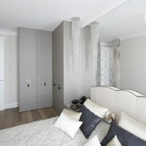 Całą ścianę za łóżkiem pokrywa ogromne lustro, którego gładka tafla przełamana została kolistymi motywami. Projekt: Karolina Łuczyńska. Fot. Bartosz Jarosz