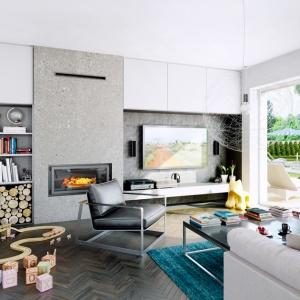 We wnętrzu Domu w kalateach wykorzystano kominek Mila, o bardzo nowoczesnej formie, oraz kratki wentylacyjne typu Luft. Zabudowa wykonana w bardzo prostej bryle, została wykończona betonem architektonicznym. Część ściany telewizyjnej jest również wykończona w ten sposób, co bardzo dobrze wpływa na odbiór całego wnętrza. Fot. archonhome.pl