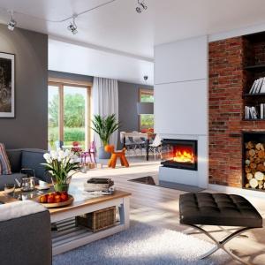 Zaletą zastosowanego w Domu w kannach narożnego kominka jest to, że ogień możemy podziwiać zarówno z części wypoczynkowej, salonowej jak i z części jadalnianej. Fot. archonhome.pl