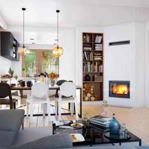 W pierwszej propozycji urządzenia domu w Czerwonokrzewach kominek Zuzia umiejscowiono w rogu salonu, a ściankę oddzielającą kuchnię wykorzystano jako miejsce na regał z książkami i drewnem kominkowym.  Fot. archonhome.pl