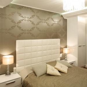 Beżowe tapety i jasny tapicerowany zagłówek dodają sypialni luksusu. Projekt: Karolina Łuczyńska. Fot. Bartosz Jarosz