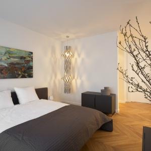 Klasyczną elegancję szarych mebli w sypialni przełamuje oryginalne oświetlenie o fantazyjnej formie. Fot. Nickel Development