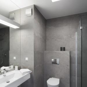 Łazienkę z wc urządzono w modnych, loftowych szarościach, nawiązując do przemysłowej przeszłości terenów, na których powstało prestiżowe osiedle. Fot. Nickel Development