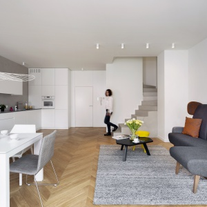 Wnętrze wizualnie ociepla drewniana podłoga z pięknych desek, ułożonych w klasyczną jodełkę, tapicerowane meble oraz szary dywan w strefie wypoczynku. Fot. Nickel Development
