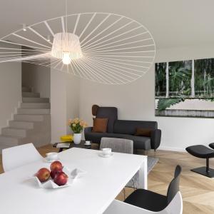 Obok mebli, imponującą dekoracją jest również oświetlenie. Designerska lampa nad stołem jadalnianym rozpościera swój ażurowy abażur, górując nad wnętrzem i przyciągając wzrok. Fot. Nickel Development