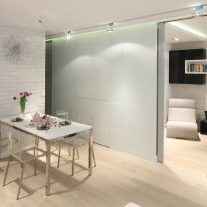 W salonie połączonym z jadalnią biała cegła zastosowana na ścianie, przy której stanął stół podkreśla skandynawski klimat wnętrza. Projekt: Monika i Adam Bronikowscy. Fot. Bartosz Jarosz