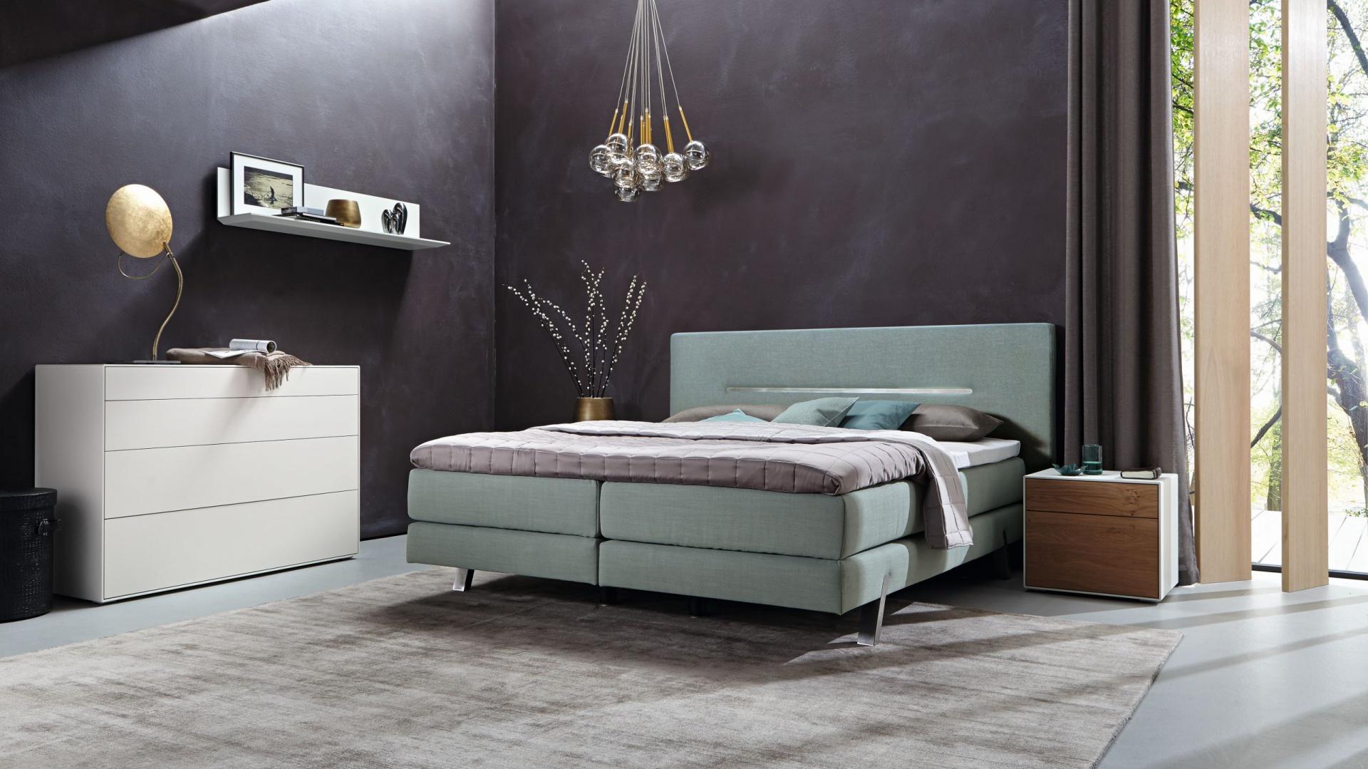 Łóżko typu boxspring z kolekcji Suite Harmony Hülsta, dostępne w tkaninowym obiciu. Dekoracyjny element na zagłówku wykonany ze stali koresponduje z wykończeniem nóżek. Fot. Hülsta