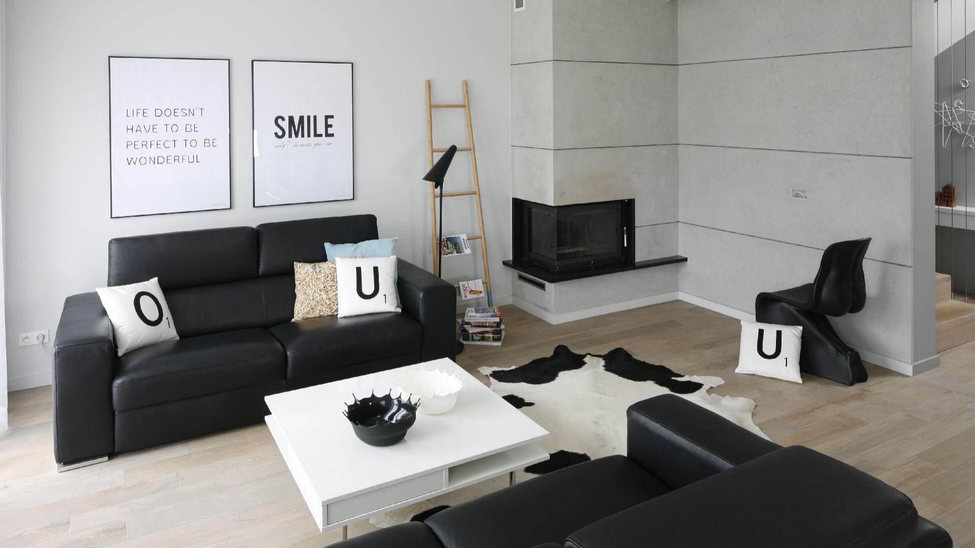Monochromatyczny czarno-biały salon prezentuje się przytulnie za sprawą miękkich mebli, skóry na podłodze oraz bladego turkusu w postaci poduszki na sofie. Projekt: Beata Kruszyńska. Fot. Bartosz Jarosz