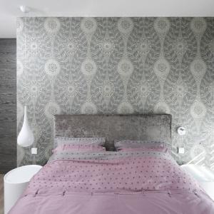 Dekoracyjna tapeta stanowi tło dla wysokiego łóżka.  Projekt: Agnieszka Ludwinowska. Fot. Bartosz Jarosz