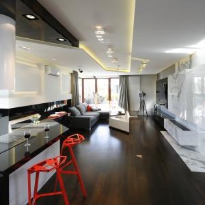 Ciemny, czekoladowy odcień podłóg kontrastuje ze śnieżną bielą ścian i podłóg. Proj. wnętrza Nasciturus Design.
