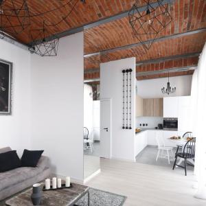 Strefę dzienną spajają wizualnie wykończenia ścian, podłogi i sufitu - w każdym pomieszczeniu takie same. Projekt: Tomasz Jasiński. Fot. Bartosz Jarosz