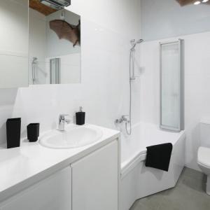 Przestrzeń niedużej łazienki optycznie powiększają lustra oraz dominująca we wnętrzu biel. Projekt: Tomasz Jasiński. Fot. Bartosz Jarosz