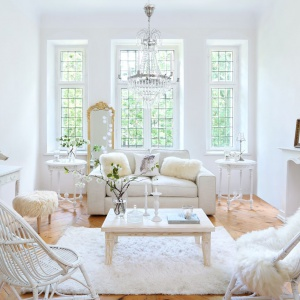 Biel wcale nie musi być sterylna, a ta aranżacja jest tego najlepszym przykładem. Bardzo przytulny salon zyskuje ciepłą atmosferę za sprawą nie tylko drewnianej podłogi, ale i mięsistej sofy, puchatych narzut, równie puchatego dywanu oraz klasycyzujących mebli. Fot. Westwing