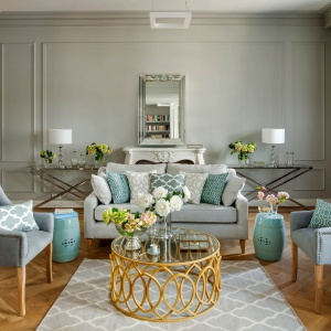 Urządzony w amerykańskim bogatym stylu salon zachwyca spokojną kolorstyką. Dominują tutaj jasne, aczkolwiek nie sterylne kolory. Szare ściane, ozdobione sztukateriami wspaniale harmonizują ze stylowymi meblami w kolorach przydymionych błękitów, zieleni i szarości. Fot. Westwing
