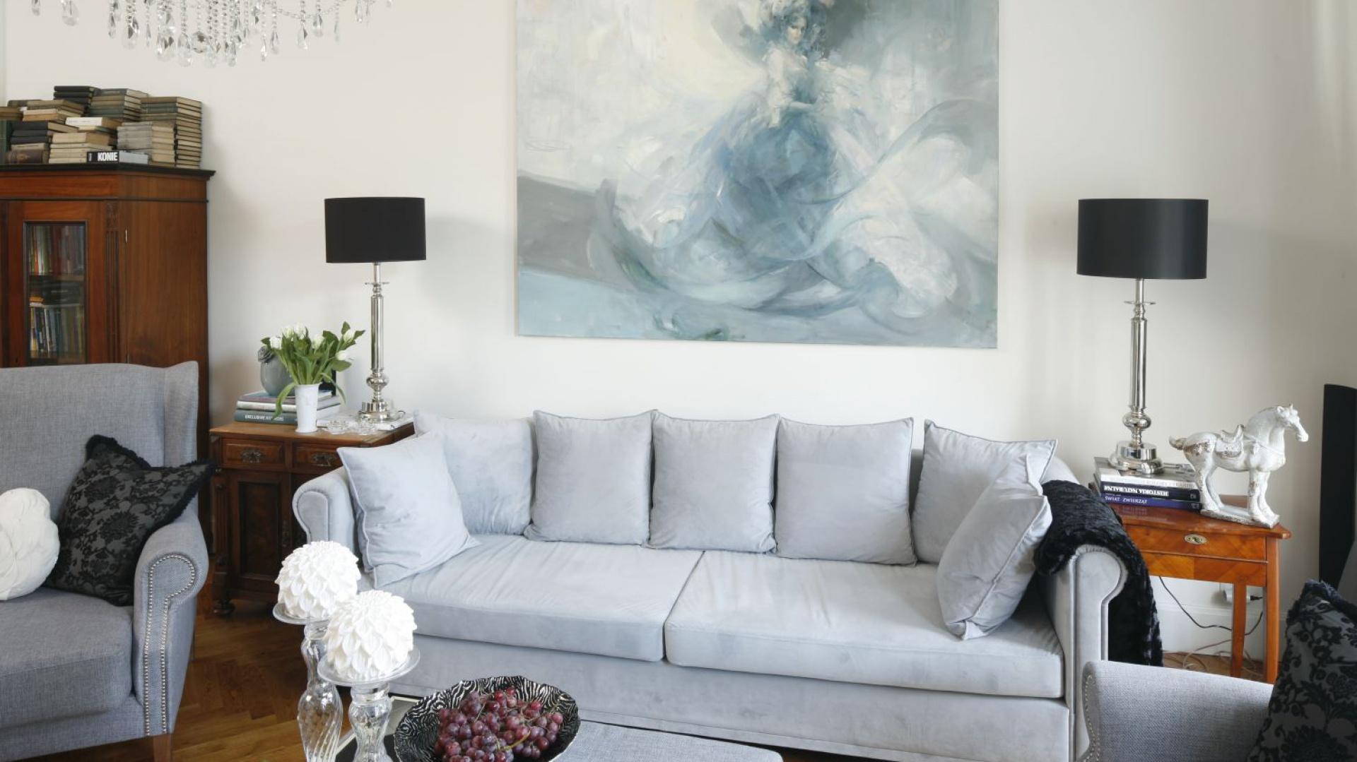 Stary drewniany regał oraz stylizowane komódki po obu stronach kanapy wpisują się w klasyczną aranżację salonu i idealnie współgrają z eleganckimi lampami na stylizowanych nogach.  Projekt: Iwona Kurkowska. Fot. Bartosz Jarosz
