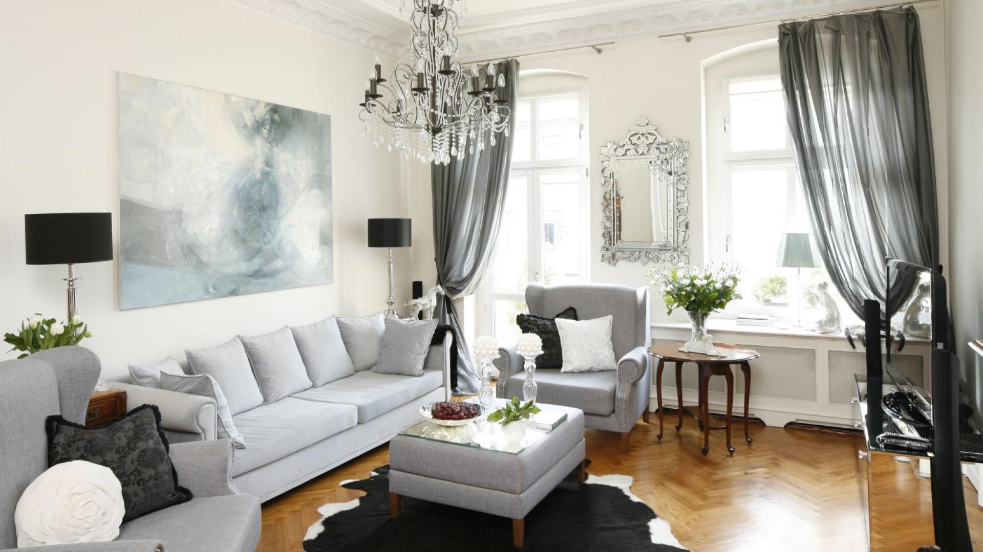 Elegancki salon w klasycznym stylu urządzono w biało-czarno-szarej kolorystyce ocieplonej drewnianą podłogą. Kryształowy żyrandol i zdobne sztukaterie idealnie wpisują się w klimat pomieszczenia. Projekt: Iwona Kurkowska. Fot. Bartosz Jarosz