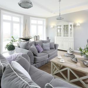 Miękkie, przytulne meble wypoczynkowe wspaniale współgrają ze stylizowanym białym regałem oraz stolikiem kawowym na dekoracyjnej podstawie. Projekt: Maciejka Peszyńska-Drews. Fot. Bartosz Jarosz