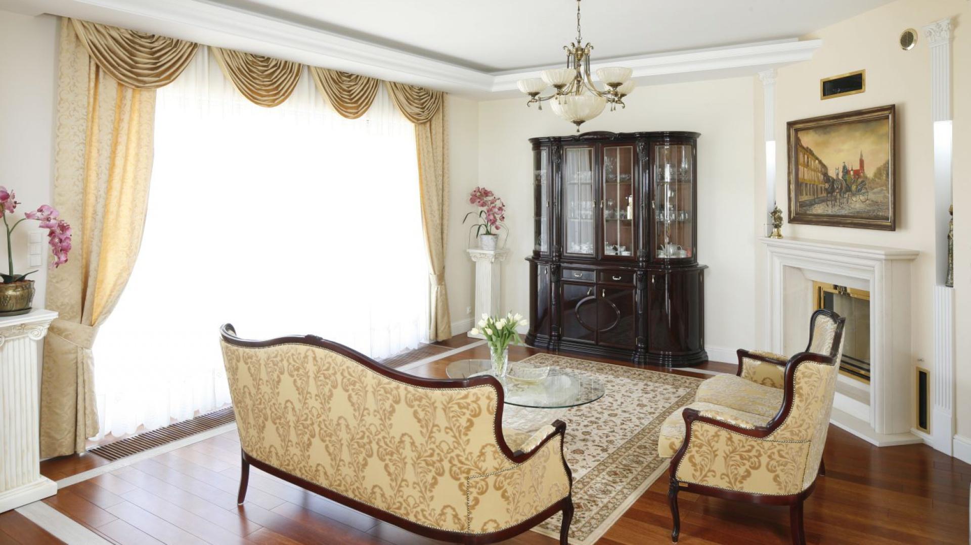 W tym salonie dominującym kolorem jest... złoto. Ubrane w klasycyzujące formy i w towarzystwie drewna w ciemnym wybarwieniu prezentuje się bardzo elegancko. Projekt: Magdalena Mirek-Roszkowska. Fot. Bartosz Jarosz