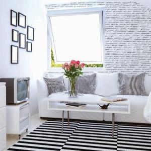 Salonik na poddaszu urządzony został w bieli i czerni, z dominacją tej pierwszej barwy, dzięki czemu jest jednocześnie elegancki i wypełniony światłem. Uroczym akcentem jest fototapeta na ścianie za kanapą z czarnymi napisami. Fot. Dekornik