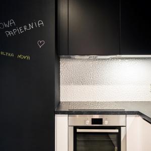 Na ścianie nad blatem ułożono płytki z fakturą 3D, które białym kolorem kontrastują z czarną zabudową kuchenną i farbą tablicową. Fot. Nowa Papiernia/Anna Kopec