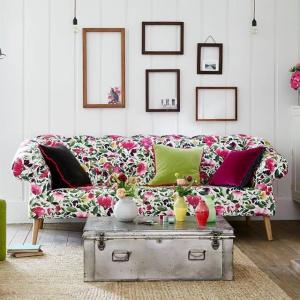 Kanapę zdobi kwiecista tapicerka, pod której kolor dobrano kolorowe poduchy - już w jednolitej barwie. Fot. Długa Showroom