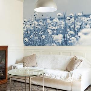 Ścianę za kanapą udekorowano błękitną fototapetą przedstawiającą łaką z kwitnącymi kwiatami. Fot. Dekornik