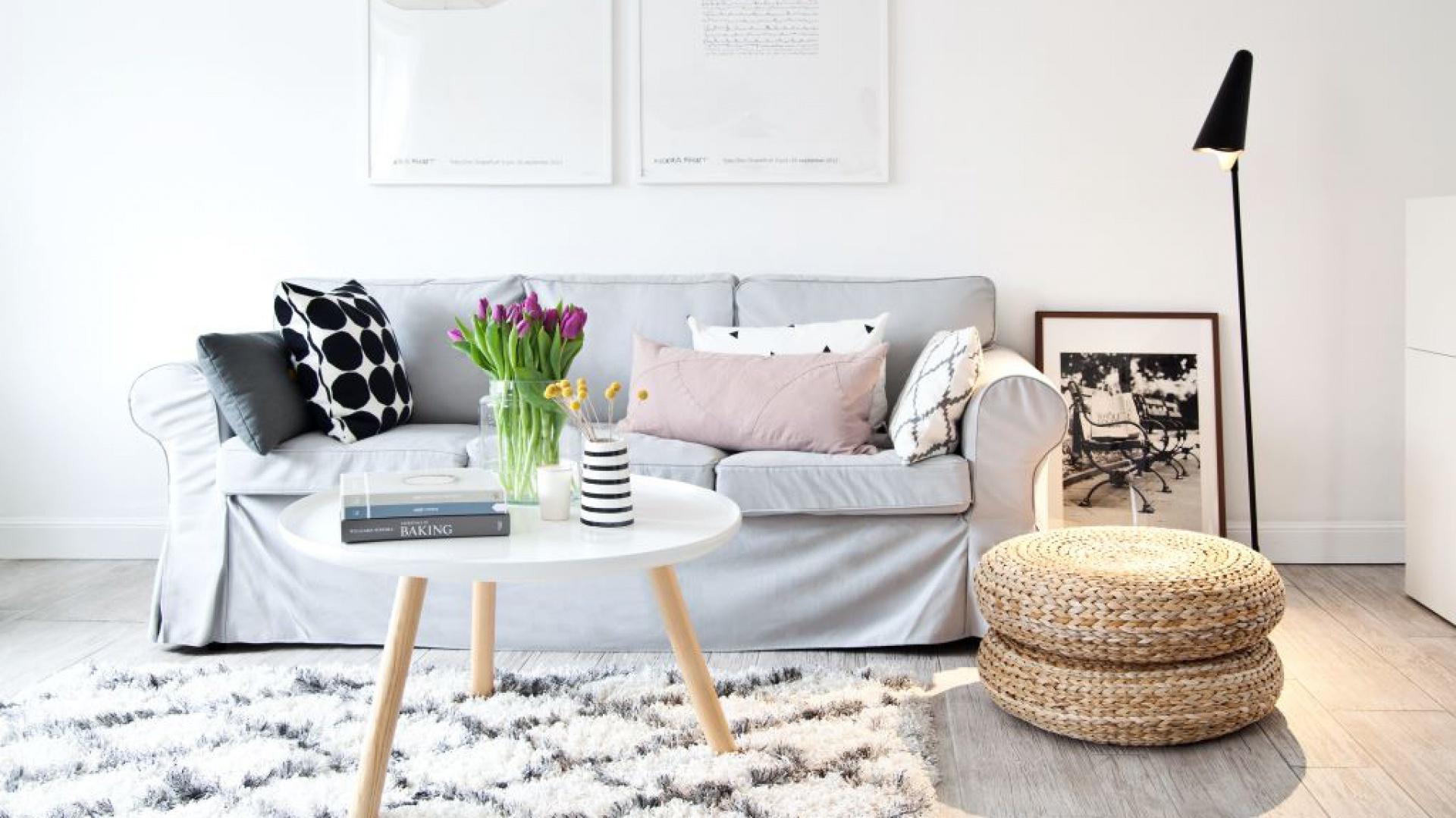 Białe ściany, jasne meble oraz wyraziste dodatki w postaci czarnej lampy podłogowej i fotografii w czarnej ramce budują w tym salonie klimat rodem ze Skandynawii. Fot. Westwing