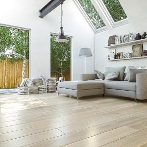 Drewniana deska w kolorze dębu Bianco idealnie pasuje do salonu w stylu skandynawskim. Całości dopełniają dodatki oraz okna pozbawione zasłon i firan. Fot. Jawor Parkiet