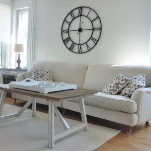 Meble wypoczynkowe w jasnych kolorach tworzą relaksującą kombinację z białymi ścianami. Skandynawski klimat podkreśla stary metalowy zegar na ścianie oraz drewniany blat stolika kawowego. Fot. Scandichic.pl