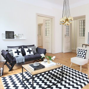 Białe ściany, duża doza drewnianych akcentów w postaci nie tylko podłogi, ale i dodatków (dekoracyjne pieńki-stoliki czy stolik kawowy), jak również czarne dodatki, duża ilość poduch i grafitowa kanapa wpisują się w skandynawską stylistykę salonu. Fot. Westwing