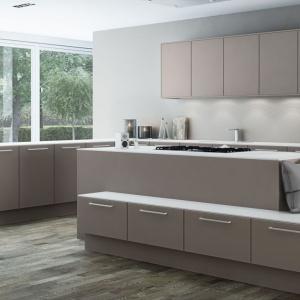 Asymetryczna wyspa kuchenna ze zintegrowanym siedziskiem, strefą gotowania oraz pojemnymi szafkami. Fot. Sigdal, kuchnia Sand