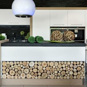 Matowe białe fronty zestawiono z ciekawym efektem dekoracyjnym w postaci ściętych pieńków drzew, a całość zdobi gruby granitowy blat w ciemnym kolorze. Fot. Pracownia Mebli Vigo, kuchnia Wood