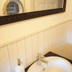 W toalecie dla gości Doroty sprawdziła się kontrastowa i minimalistyczna, biało-czarna tonacja. Nie było tu miejsca na przesadę aranżacji i kolorów, wnętrze podkreśliła jedynie czarna roleta, proste grafiki na ścianach i lustro w ozdobnej ramie.