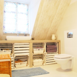 W klimatycznej łazience na poddaszu znalazły się elementy z recyklingu. Pod blatem ustawiono stylizowane drewniane skrzynki, pomalowane białą, przecieraną farbą. Projekt: Dorota Szelągowska, Fot. Cersanit