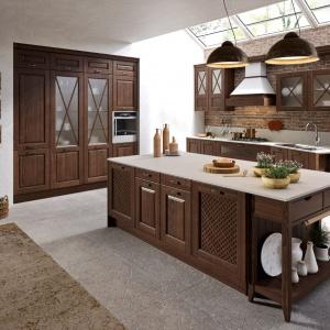 Elegancka kuchnia w stylu klasycznym wykonana z drewna w czekoladowym wybarwieniu. Nie zabrakło tutaj zarówno frezowań, szprosów na przeszkleniach, jak i ażurowych drzwiczek. Fot. Aran Cucine, kuchnia Bellagio