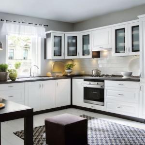 Frezowane fronty, przeszklone szafki górne, dekoracyjne uchwyty, a także oryginalne obramowanie zabudowy w ciemnym kolorze tworzą elegancką, klasyczną aranżację. Fot. Black Red White, kuchnia Older