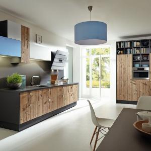 Fronty zabudowy kuchennej zdobi ciekawy wzór starej deski w jasnym odcieniu drewna. Otaczają je ciemnoszare ramy. Fot. Sachsen Kuechen