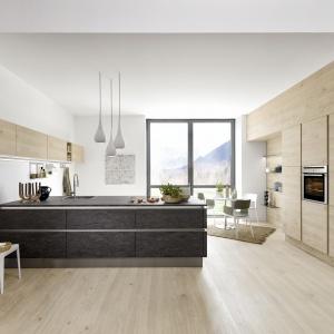 Piękna nowoczesna kuchnia od marki Nolte Kuechen zachwyca prostotą form i elegancką kolorystyką. Drewno w ciepłym, jasnym wybarwieniu kontrastuje z wyspą kuchenną o frontach z drewnianym dekorem w ciemnym kolorze szarobrązowym. Fot. Nolte Kuechen