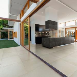 Ceramiczny gres położony na tarasie jest taki sam, jak płytki w salonie, co w elegancki sposób spaja te dwie przestrzenie wizualnie. Fot. Keraben