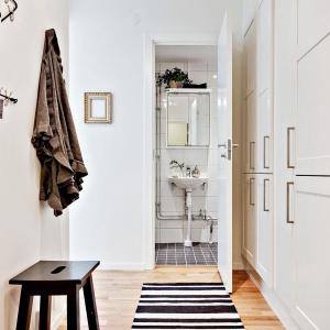 Ścianę w niewielkim holu zabudowano szafkami pod sam sufit. Pojemna zabudowa pozwoliła zrezygnować z ciężkiego umeblowania w przestrzeni salonu z sypialnią. Fot. Svenskfast