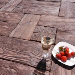 System dekoracyjny Pino  firmy Buszremto zestaw elementów betonowych wiernie odzwierciadlający deski, belki i pieńki z   sosnowego drewna. W skład systemu wchodzą trzy rodzaje desek, dwie palisady i dwa elementy przypominające  plastry przeciętego pnia. Fot. Buszrem
